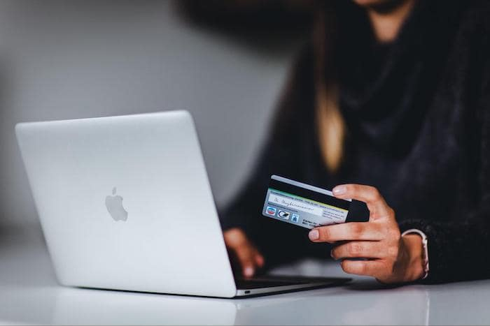 A person using a laptop and credit card to shop online